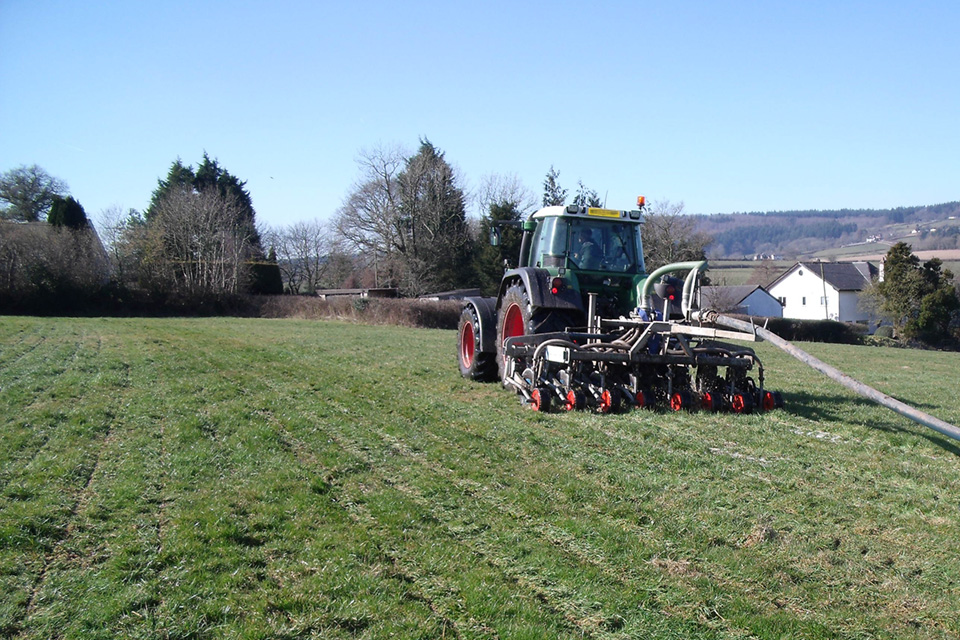 Tractor with slurry injector umbilical system on a field in Devon